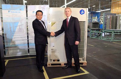 David Swift, (left) the CEO and president of Goodman and the head of Daikin's North American operations, and Takeshi Ebisu, a senior executive officer and a member of Daikin's board, cut a ribbon at the Daikin manufacturing line in Houston