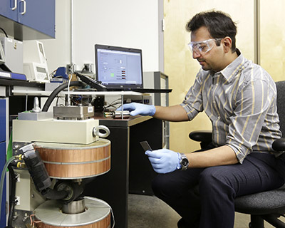 """ORNL's Ayyoud Momen works on the team's """"breadboard"""" prototype refrigerator-freezer: a flexible platform used to evaluate material compatibility and to analyse components including the magnet, generators, motor, pump, heat exchangers, plumbing and leakless rotating valve"""